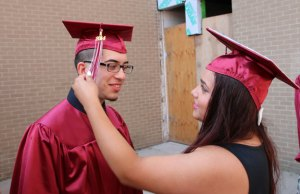 Naugatuck High School Class of 2014 graduate Janelle Luevano fixes the tassel on classmate Carlos Ayala's cap Tuesday afternoon at the high school before graduation. –LUKE MARSHALL