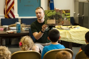 Keith Syrett with the Department of Energy and Environmental Protection reads a story to young children at the Beacon Falls Library Tuesday. The children made nature journals afterward and checked out various finds from nature on display. –RA ARCHIVE