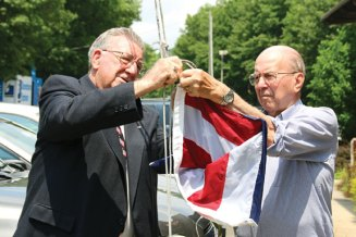 U.S. Air Force veteran Robert Stauffer, left, and U.S. Navy veteran Horace Cushman attach an American flag to the flagpole outside the Naugatuck Historical Society July 3. The flag was flown over the U.S. Capital on May 30 before being given to the society. Society President Wendy Murphy thanked U.S. Sen. Chris Murphy (D-Conn.) and Naugatuck Economic Development Corporation CEO Ron Pugliese for helping to procure the flag. –LUKE MARSHALL