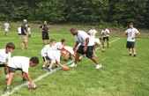 Former NFL quarterback Daunte Culpepper provides some tips as he runs a drill during the Bags All-Star Football Camp hosted by the Woodland Jr. Hawks July 19 at Caplan Park in Prospect. Culpepper, who played 11 seasons in the NFL, worked with campers on proper stances and on how to throw a pass. –LUKE MARSHALL