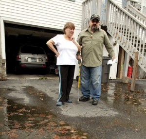 Maria Novo, left, and her son Americo Novo stand in front of the duplex home they share on Andrews Avenue in Naugatuck where water has damaged the home. The Novo's claim that after construction work on the Garden Homes Management Corporation owned apartment complex last year, water has been a problem on their property and has damaged their home. –RA ARCHIVE