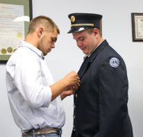 Adam Siemenski, left, pins a medal on the chest Matthew Rau during the Beacon Falls Board of Selectmen meeting Aug. 11. Rau was sworn in as Beacon Hose Company No. 1's new assistant secretary.-LUKE MARSHALL