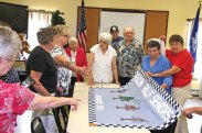 Members of the Beacon Falls and Oxford senior centers unfurl a new banner at the Beacon Falls Senior Center July 23. The members of the Oxford Senior Center made the new banner for the Beacon Falls Senior Center to replace an old one that was falling apart. –LUKE MARSHALL