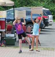 Olivia Sewitsky, 8, left, and Lauren Mulinski, 11, both of Beacon Falls, promote the United Day School's lemonade stand July 24 along Main Street in Beacon Falls. For the past four years, children in the school's summer program have sold lemonade to benefit an organization in town. This year the money raised will go the Beacon Falls Senior Center. –ELIO GUGLIOTTI