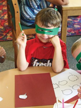 Jacob McGrath, 4, of Naugatuck designs a speech bubble to go with a superhero at the Whittemore Library in Naugatuck July 23. The library handed out capes and masks for the children to wear as part of Superhero Week. The weeklong celebration, which was in honor of the 75th anniversary of the creation of Batman, included a superhero parade and screening of the 1966 Batman: The Movie. –LUKE MARSHALL