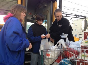 From left, Jackie Froliger, Marco Mendes and Stacy McKenney fill a carriage for the Naugatuck Ecumenical Food Bank Sunday. Froliger and McKenney work for Student Transportation of America, Naugatuck's school bus company, which held fill a bus events at Stop & Shop and Wal-Mart in Naugatuck on Sunday. -REPUBLICAN-AMERICAN
