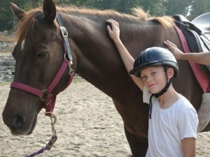 Ryan Setaro, 9, of Beacon Falls, stands next to a horse at Hidden Acres Therapeutic Riding Center in Naugatuck. Last year, the center served more than 200 children and adults with physical, developmental and emotional challenges. -CONTRIBUTED
