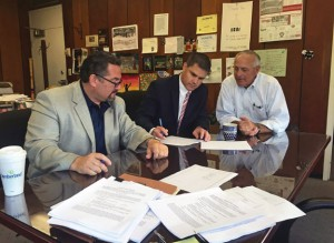 Mayor Robert Mezzo, center, signs a contract that will allow for development of Parcel C in downtown Naugatuck Sept. 3 at his office in Town Hall. With him are developer Rob Oris, left, a Naugatuck native who wants to build a medical office complex and restaurant at the vacant site, and Naugatuck Economic Development Corporation President and CEO Ron Pugliese.-REPUBLICAN-AMERICAN