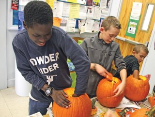 From left, Kelvin Essilfie, 12, Ryan Setaro, 10, and Adam Setaro, 8, all of Beacon Falls, scoop out the insides of pumpkins during the Beacon Falls Library's pumpkin carving event Oct. 29. –LUKE MARSHALL