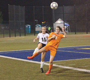 Woodland's Eliza Smith (11) clears the ball as Watertown's Erin Hughson rushes in during the NVL girls soccer tournament final Nov. 5 at Municipal Stadium in Waterbury. Woodland won, 2-1. –ELIO GUGLIOTTI