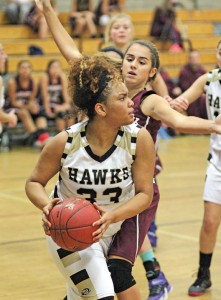 Woodland's Camryn Johnson (33) looks for an open teammate after pulling down a rebound as Naugatuck's Mia Rotatori defends Dec. 18 in Beacon Falls. Woodland won the game, 41-27. –ELIO GUGLIOTTI