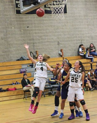Woodland's Maddie Hupprich (4) lays up a shot as Jenna Pannone (24) boxes out Kennedy's Sarah Norwood and Destiny Prather Dec. 23 in Beacon Falls. Woodland won the game, 64-56. –ELIO GUGLIOTTI