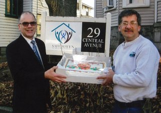 Lee Schlesinger, left, executive director of Safe Haven of Greater Waterbury, accepts a cake donated by Costco in Waterbury. The cake was for the Thanksgiving dinner Naugatuck resident Dan Whitman, right, has sponsored for a number of years. This year, Joe Cantone and John Ricciardone, owners of the Manor Inn in Southington, prepared a catered traditional holiday dinner for 20 people staying at the domestic violence shelter. -CONTRIBUTED