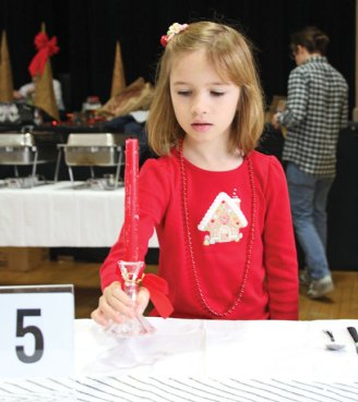 Sofia Sargent, 7, of Beacon Falls, helps to set up a table Christmas Eve morning at St. Michael's Church in Naugatuck in preparation for the Joy of Christmas Dinner. The annual dinner, which was served on Christmas, is hosted by a committee of volunteers and open to anyone who wanted to share a meal on the holiday. –LUKE MARSHALL