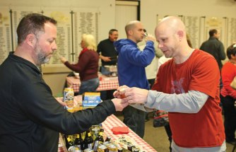 Dan Zeek from Two Roads Brewery in Stratford, left, hands a sample of one of the brewery's beers to Chris Kiernan, of Naugatuck, Feb. 13 during the Naugatuck Historical Society's annual Savor CT at the Naugatuck Elks Lodge. The event featured samples of food and alcohol made in Connecticut. About 190 tickets were sold for the event, which was more than double last year's ticket sales, according to historical society Treasurer Wendy Murphy. –LUKE MARSHALL