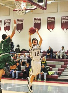 Naugatuck's Andre Trosan (12) lays in a basket as Bassick's Davonte Whitehurst (1) comes in to defend Jan. 28 in Naugatuck. Bassick won the game, 81-63. –ELIO GUGLIOTTI