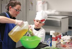 Salem Elementary School fourth-grader Laurence Northrup, right, measures oil for his banana and strawberry pancake delight with the help of Naugatuck High School food services worker Kristi Daigle during the Sodexo Future Chef competition March 9 at Naugatuck High School. –ELIO GUGLIOTTI