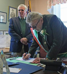 Prospect's honorary Irish Mayor of the Day Ed Flynn signs a copy of the town's proposed budget March 17 in the mayor's office at Prospect Town Hall as Prospect Mayor Robert Chatfield looks on. –ELIO GUGLIOTTI
