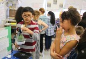 Cross Street Intermediate School fifth-grader Adrian Ocampo, left, shows off his invention, the Vac-Brush, to fifth-grader Ayana Williams March 31 during the school's Invention Convention. –LUKE MARSHALL