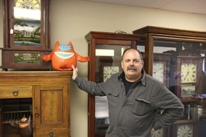 Naugatuck Historical Society President Ken Hanks stands in front of some of the permanent displays at the society's temporary museum at 171 Church St. while holding a 'Nauga,' the mascot Uniroyal used to promote Naugahyde, which was first made in the borough. The historical society is hosting a museum debut on May 6. –LUKE MARSHALL