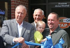 From left, Naugatuck Mayor N. Warren 'Pete' Hess, Naugatuck Economic Development Corporation President and CEO Ron Pugliese, and Wing It On owner Michael Woodruff, holding his grandson, prepare to cut a ribbon March 24 to celebrate the opening of the Wing It On TAP restaurant at 175 Church St. in Naugatuck. –LUKE MARSHALL