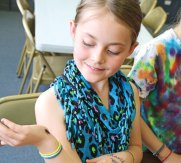 Leah Feeney, 9, of Beacon Falls, watches a mealworm beetle crawl on her hand during the Insect Investigation program co-sponsored by the Beacon Falls Library and the Beacon Falls Parks and Recreation Department April 22 in Beacon Falls. –LUKE MARSHALL