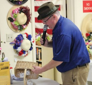 Naugatuck Mayoral Aide Ed Carter rolls the dice during the Naugatuck Senior Center's annual Kentucky Derby Day May 6. The event featured a 'horse' race in which members of the center and volunteers acted as 'horses' and moved closer to the finish line with a roll of the dice. –ELIO GUGLIOTTI