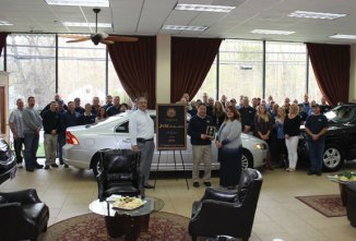 Peter Saldamarco, foreground left, president of the Connecticut Independent Auto Dealers Association, or CTIADA, and Debbie Wright, foreground right, executive director of CTIADA, present the organization's 2016 Connecticut Quality Dealer Award to James McCowan, center, owner of J&M Automotive Sales & Service in Naugatuck, during a ceremony at the dealership on May 5 as the dealership's staff looks on. –CONTRIBUTED