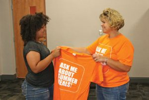 Naugatuck Public Schools Food Service Director Kate Murphy, right, hands volunteer Alessia Palermo, 13, a T-shirt June 24 before a meeting on the free summer meals program at the Board of Education office. Volunteers, including Palermo, handed out information throughout the borough on the program following the meeting. –LUKE MARSHALL