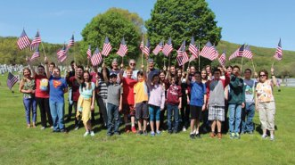 A group of City Hill Middle School students helped veterans replace over 1,700 American flags at the graves of veterans at St. James Cemetery in Naugatuck prior to Memorial Day. -CONTRIBUTED