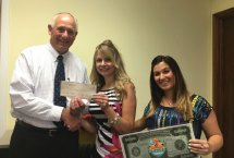 Ron Pugliese, CEO of the Naugatuck Economic Development Corporation and chairman of the Naugatuck Chamber of Commerce, left, and Courtney Ligi, director of the Naugatuck Chamber, right, present Jean Carr, of Naugatuck, with $5,000 for having the winning duck in the chamber's annual duck race. -CONTRIBUTED
