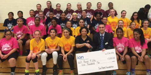 Ion Bank Executive Vice President David Rotatori presents a $1,000 donation to Director of Hoops4Life Deneen Fryer surrounded by girls basketball players. The Ion Bank Foundation donated the money to Hoops4Life, a Waterbury-based nonprofit organization that provides athletic and educational programs for youth. -CONTRIBUTED