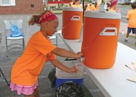 United Day School student Lauryn Massa, 7, of Prospect, pours a glass of lemonade for a customer July 14 during the school's annual lemonade stand in Beacon Falls. Each year students sell lemonade in the parking lot next to Beacon Hose Company No. 1 to raise money for different causes. This year 28 students helped sell lemonade and raised $400. A portion of the money will be donated to Beacon Hose and a portion will be used to send care packages to soldiers serving abroad. –LUKE MARSHALL