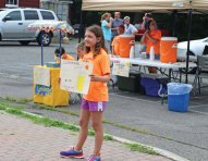 United Day School student Isabella Paupini, 10, of Beacon Falls, holds a sign July 14 advertising the school's annual lemonade stand in Beacon Falls. Each year students sell lemonade in the parking lot next to Beacon Hose Company No. 1 to raise money for different causes. This year 28 students helped sell lemonade and raised $400. A portion of the money will be donated to Beacon Hose and a portion will be used to send care packages to soldiers serving abroad. –LUKE MARSHALL