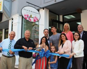 Peach Blossom Boutique and Gifts at 175 Church St. in Naugatuck celebrated its opening with a ribbon cutting ceremony on June 29. Pictured, from left, Naugatuck Economic Development Corporation President and CEO Ronald Pugliese, Mayor N. Warren 'Pete' Hess III, Peach Blossom owner Margi Vance with her husband, Patrick Vance, and their children, Ethan and Elizabeth Vance, Naugatuck Chamber of Commerce Director Courtney Ligi, Burgess Laurie Taf-Jackson, state Rep. Rosa Rebimbas and Burgess Rocky Vitale. –CONTRIBUTED
