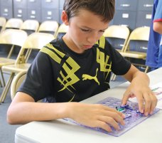 Daniel Sargent, 13, of Beacon Falls, works on creating an electronic circuit which will light a lightbulb on Aug. 11 during the Explore Circuits program at the Beacon Falls Library. The program is part of the library's initiative to bring more science, technology, engineering, and mathematic programs to the community. –LUKE MARSHALL