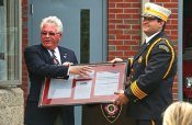 Prospect Mayor Robert Chatfield, left, presents a framed copy of the last mortgage payment on the firehouse, the vote to approve the building of the firehouse, and the letter bank saying the mortgage is paid off to Assistant Fire Chief William Lauber July 30 during a mortgage burning ceremony at the firehouse. The town paid off the mortgage on the firehouse, which was built in 1996, in July and hosted a mortgage burning ceremony with current members and past chiefs to celebrate. –LUKE MARSHALL