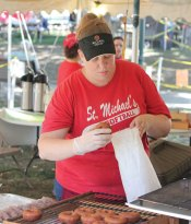 Volunteer Megan Rivers bags homemade donuts Sept. 9 during the 57th Annual Village Green Fair hosted by St. Michael's Church on the Naugatuck Green. The annual fair featured music, children's activities, food and household items for sale. –ELIO GUGLIOTTI
