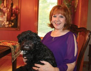 Author Liz Falzone and her dog, Shilo, are pictured at their home in Beacon Falls. Falzone published her second book, 'Flutters of Evil,' this summer. –LUKE MARSHALL