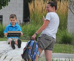 The new school year started Aug. 25 in Naugatuck and Region 16. Toni Ciarleglio laughs after taking a picture of her 5-year-old son, Evan, before his first day of kindergarten at Prospect Elementary School Aug. 25. –ELIO GUGLIOTTI