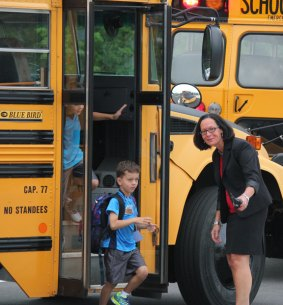 The new school year started Aug. 25 in Naugatuck and Region 16. Prospect Elementary School Rima McGeehan greets and directs students as they get off the bus on the first day. –ELIO GUGLIOTTI