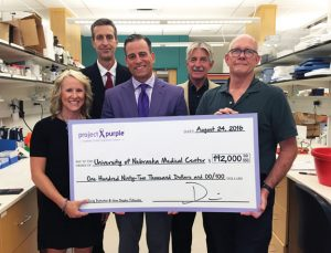 Project Purple recently awarded grants totaling $192,000 to the University of Nebraska Medical Center. Pictured, from left, Project Purple board member Elli Erickson, Tom Thompson from the University of Nebraska Medical Center, Project Purple founder and CEO Dino Verrelli, Lincoln Track Club President Glen Moss and Dr. Michael Hollingsworth from the medical center. –CONTRIBUTED