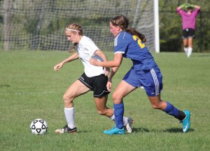 Woodland's Megen Sirowich (12) fends off Seymour's Fiona Smith (24) Sept. 9 in Beacon Falls. Woodland won the game, 7-0. –ELIO GUGLIOTTI