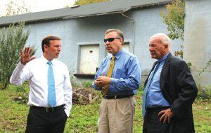 U.S. Sen. Chris Murphy, D-Conn, left, talks with Beacon Falls First Selectman Christopher Bielik, center, and state Sen. Joseph Crisco, D-Woodbridge, about a brownfield property at 100 Railroad Ave. in Beacon Falls Oct. 13. –LUKE MARSHALL