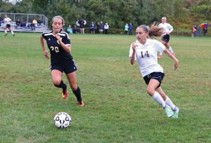 Woodland's Shannon Pruzinsky (14) races Jonathan Law's Kristen Passaro (20) to the ball Sept. 30 in Beacon Falls. Woodland won the game, 4-0. –LUKE MARSHALL