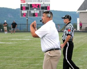 Woodland head football coach Chris Moffo sends in the defensive signals early this season. Moffo, who has been an assistant with the team since 2007, was handed the reins in the spring when he was named head coach. –ELIO GUGLIOTTI