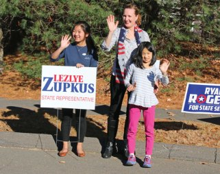 State Rep. Lezlye Zupkus, R-Prospect, along with her two daughters, Reagan Zupkus, 9, right, and Aizlyn Zupkus, 16, wave to people heading to the polls to vote on Nov. 8 at the Prospect firehouse. Zupkus, who was running unopposed, was re-elected in the 89th House District. –LUKE MARSHALL