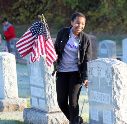 City Hill Middle School seventh-grader Kanny Salike holds flags that need to be replaced while pulling another one from a grave Nov. 1 at St. James Cemetery in Naugatuck. Students participated in an annual program coordinated by local veterans and the school to replace the flags at veterans' graves in the cemetery before Veterans Day. Nearly 1,700 veterans are buried in the cemetery. About 30 middle school students came out to help replace the flags. Students also help replace the flags before Memorial Day. –ELIO GUGLIOTTI