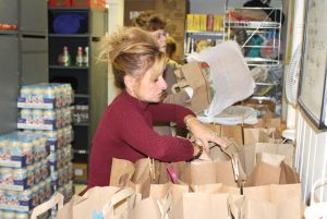 Volunteer Patricia Parenti fills bags Oct. 28 at the Naugatuck Ecumenical Food Bank on Spring Street. –LUKE MARSHALL