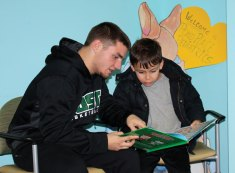 Post University men's basketball player Tyler Collodel, of Prospect, reads to Xander Ramalhete, Prospect, recently during a pajama storytime at Pond Place Pediatrics in Prospect. Members of the basketball team participated in the event, which was run in conjunction with St. Mary's Hospital, and contributed funds for the purchase of books for each child to take home. –CONTRIBUTED
